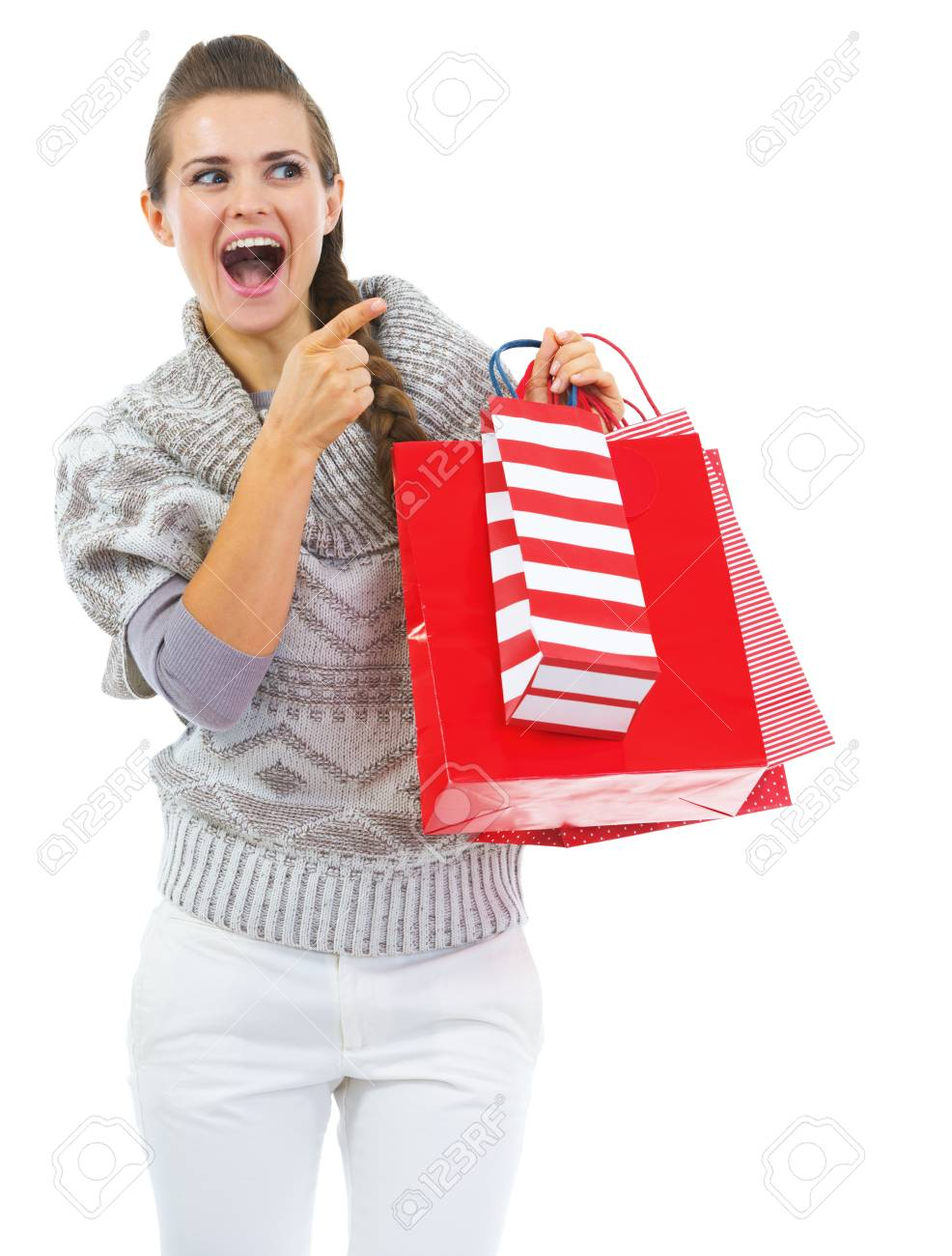 Surprised young woman in sweater with shopping bags pointing on copy space Stock Photo - 21792298