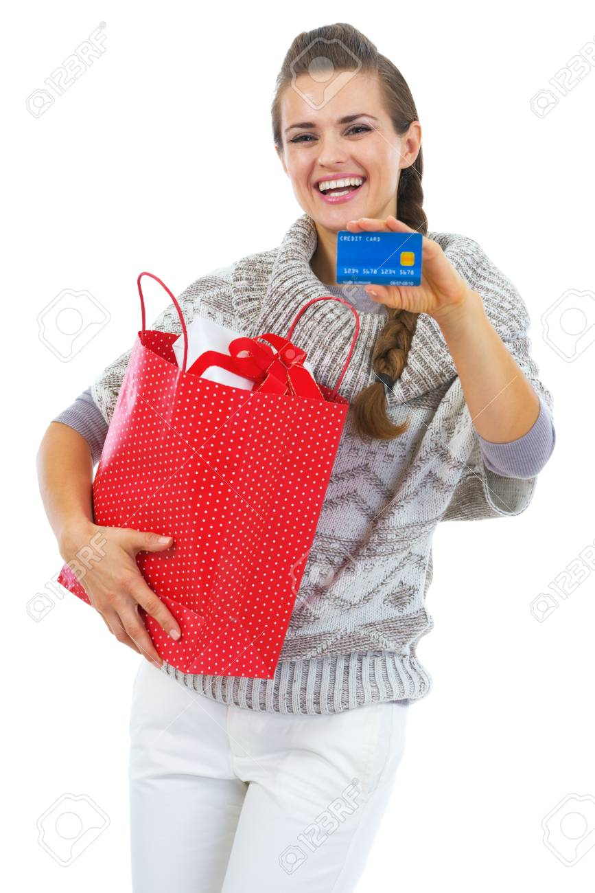 Happy young woman in sweater with christmas shopping bag showing credit card Stock Photo - 21792312