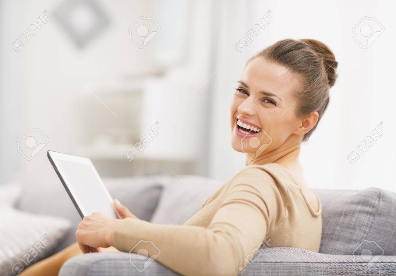Smiling young woman with tablet pc sitting on sofa Stock Photo - 21792397