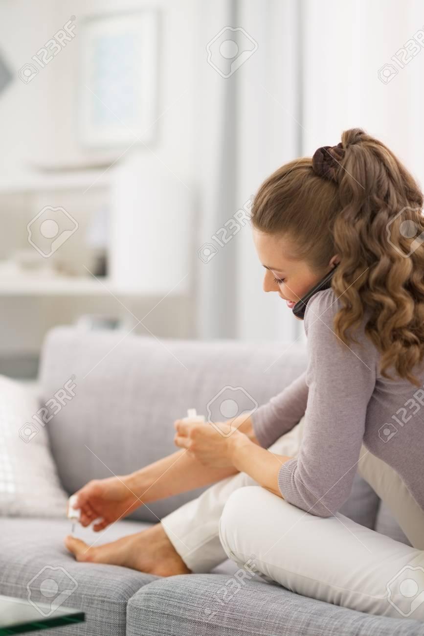 Young woman applying nail polish while talking cell phone . rear view Stock Photo - 21792450