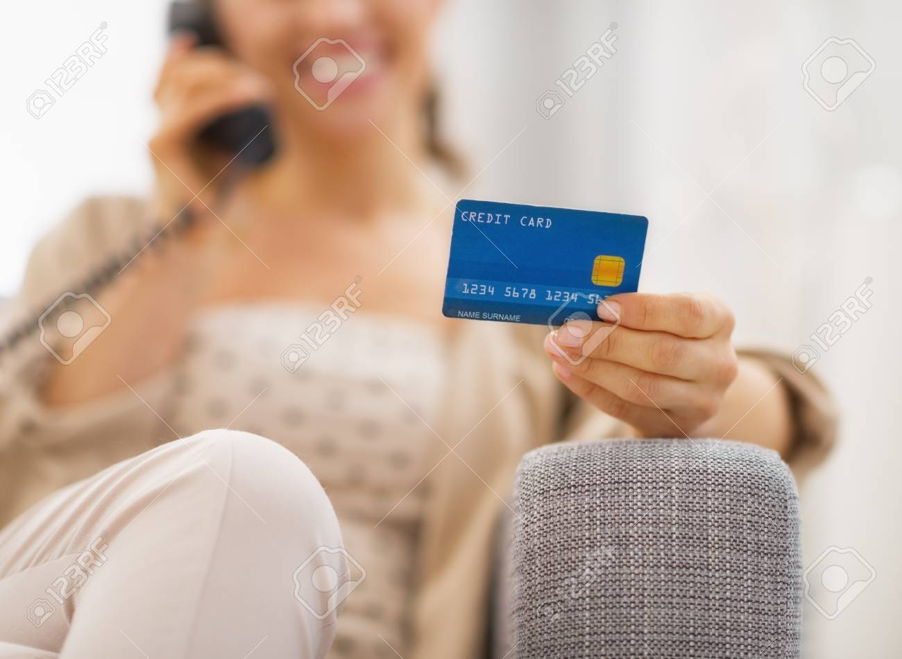 Closeup on credit card in hand of young woman talking phone Stock Photo - 21792478