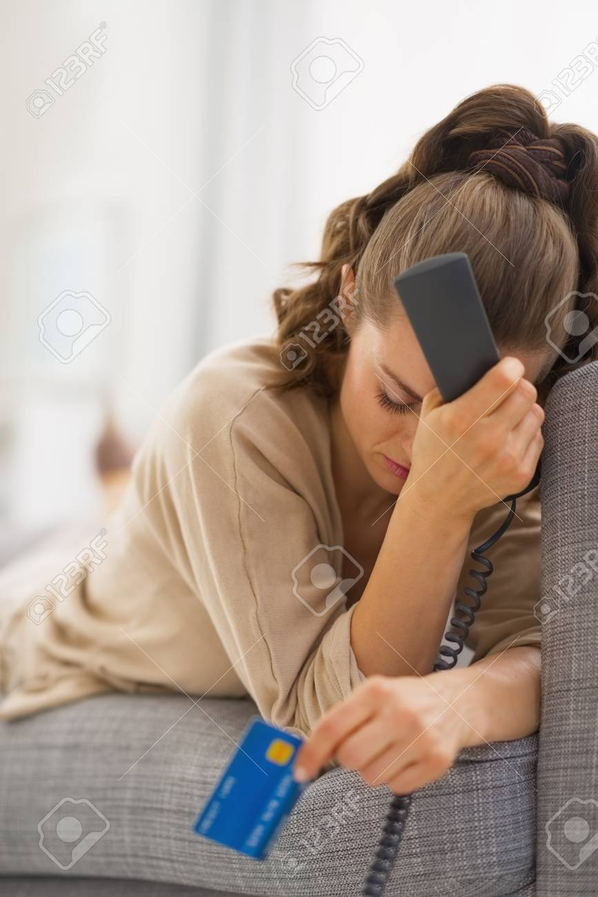 Stressed young woman with phone and credit card Stock Photo - 21792483
