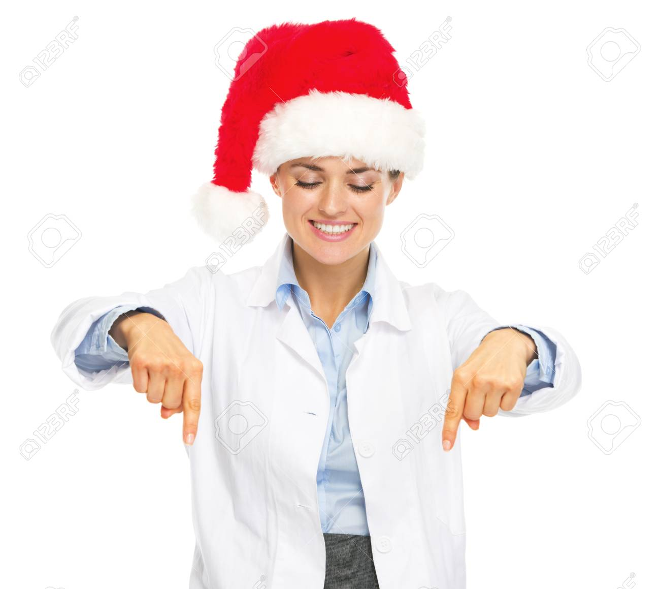 Smiling doctor woman in santa hat pointing down on copy space Stock Photo - 21949731