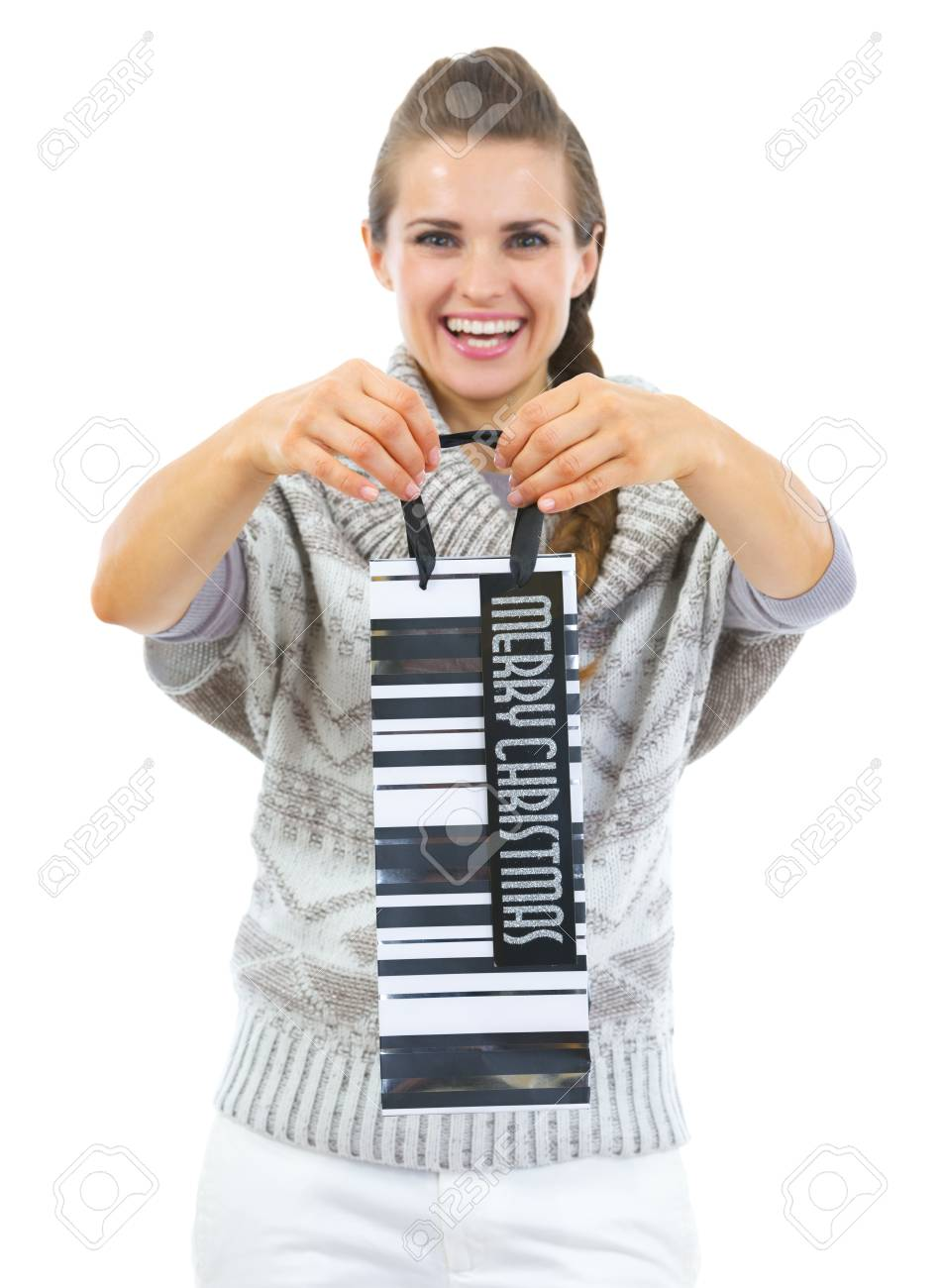 Closeup on christmas shopping bag in hand of smiling young woman in sweater Stock Photo - 22518719