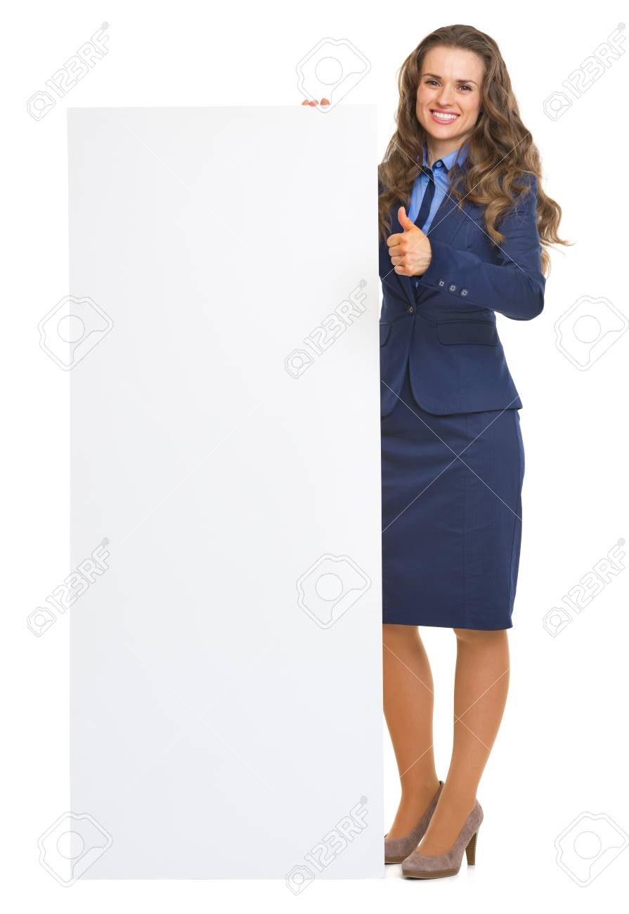 Full length portrait of smiling business woman showing blank billboard and thumbs up Stock Photo - 22665510