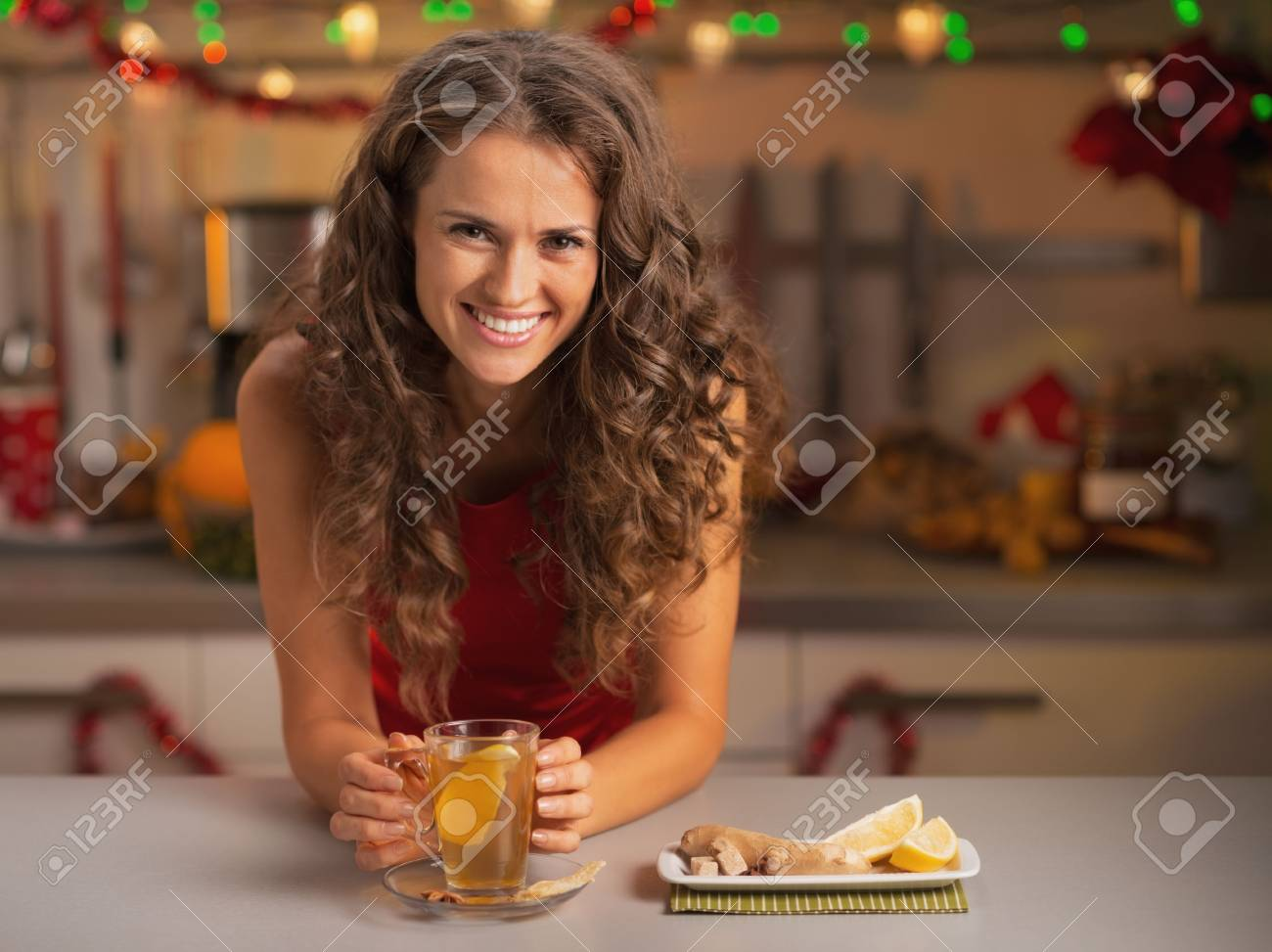 Smiling young woman drinking ginger tea in christmas decorated kitchen Stock Photo - 22887968