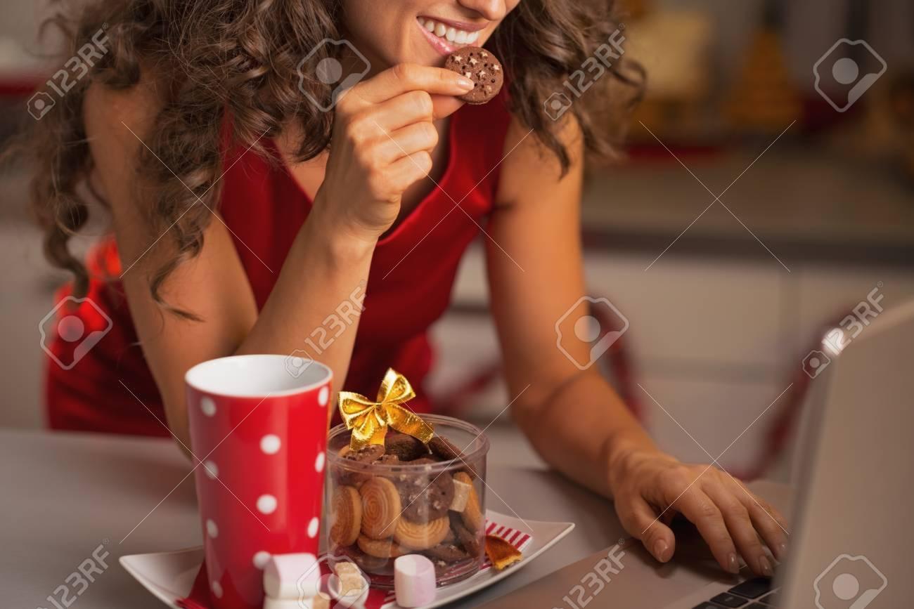 Closeup on happy woman having christmas snacks and usign laptop Stock Photo - 22887887