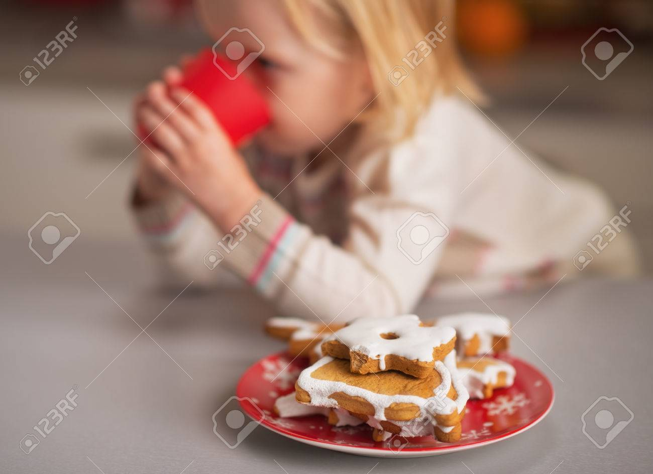Closeup on homemade christmas cookies and baby drinking milk in background Stock Photo - 23533211