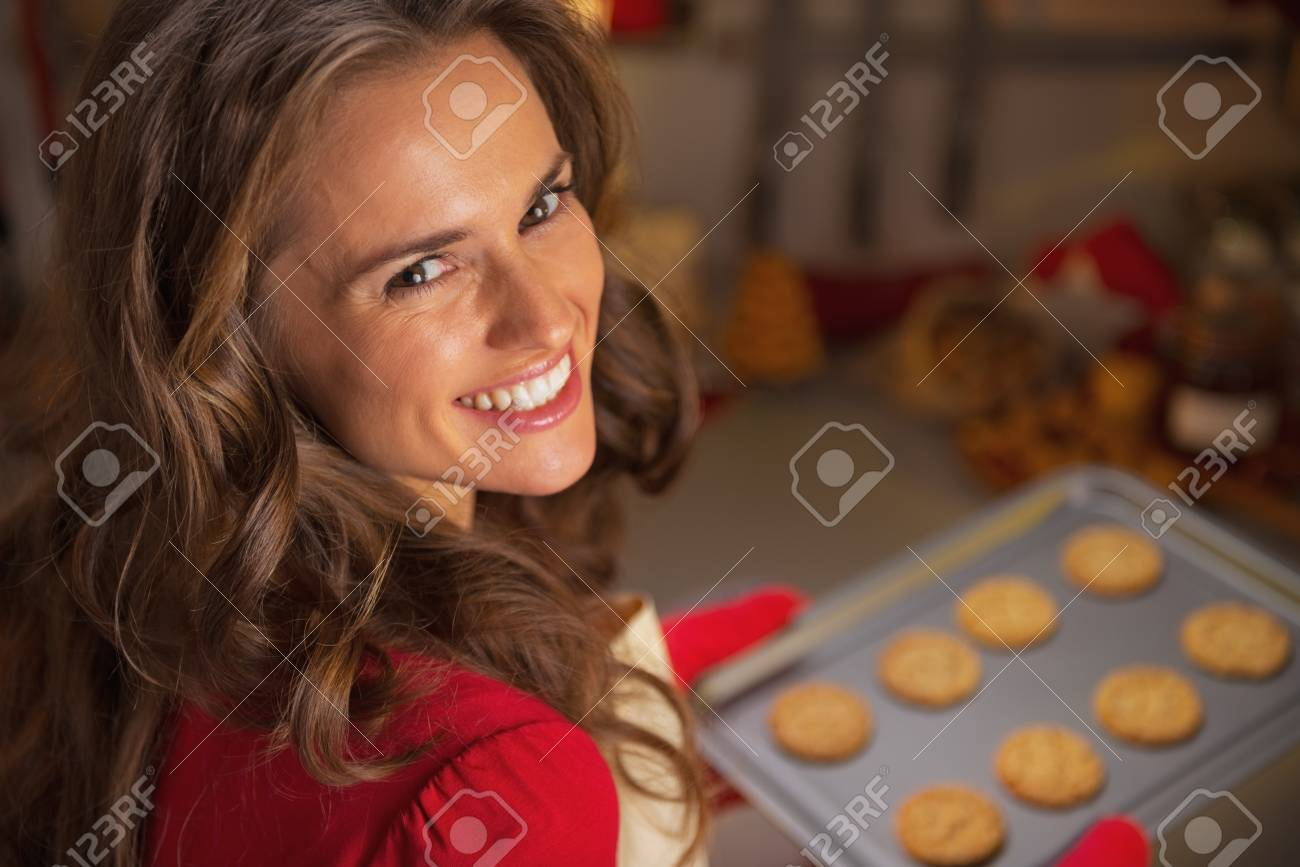 Portrait of happy young housewife holding pan with christmas cookies Stock Photo - 23533218