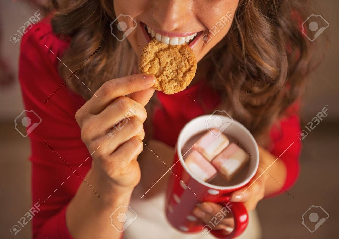 Closeup on happy young housewife drinking hot chocolate and eating christmas cookie Stock Photo - 23533294
