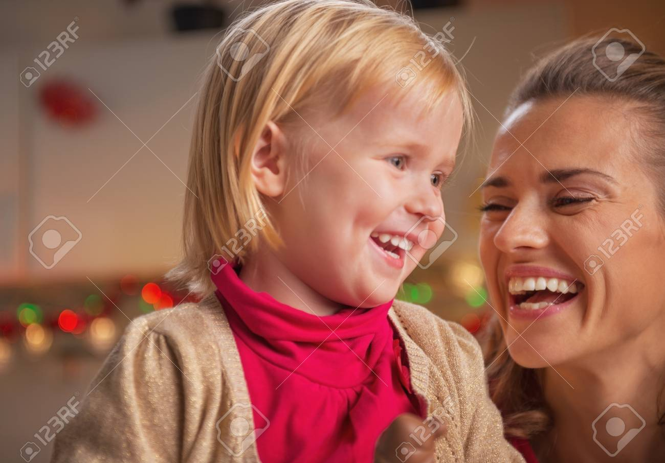 Portrait of smiling mother and baby in christmas decorated kitchen Stock Photo - 23533498