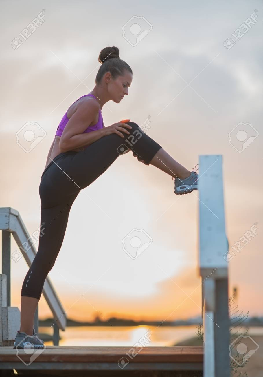 Healthy young woman stretching outdoors in the evening Stock Photo - 23537183
