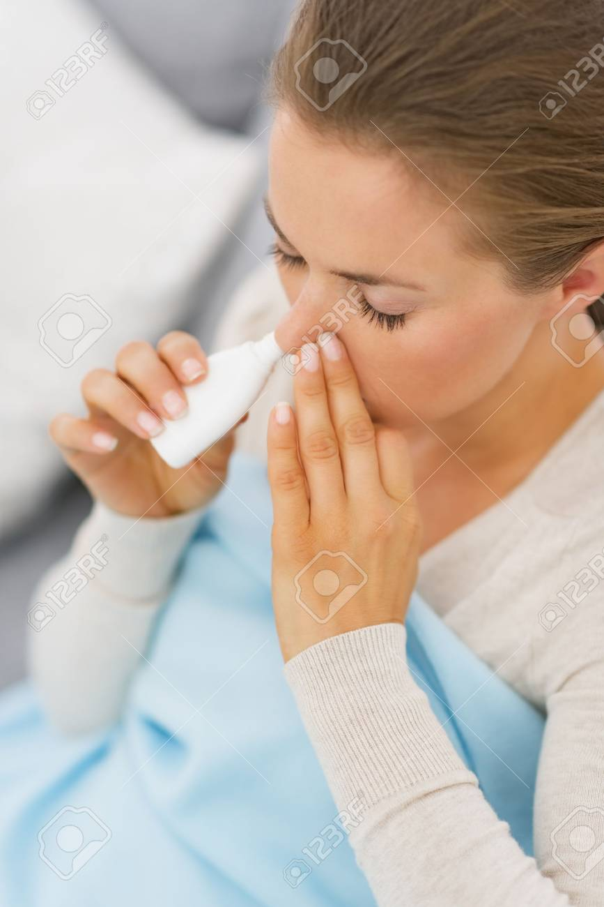 Young woman using nose drops Stock Photo - 25398242