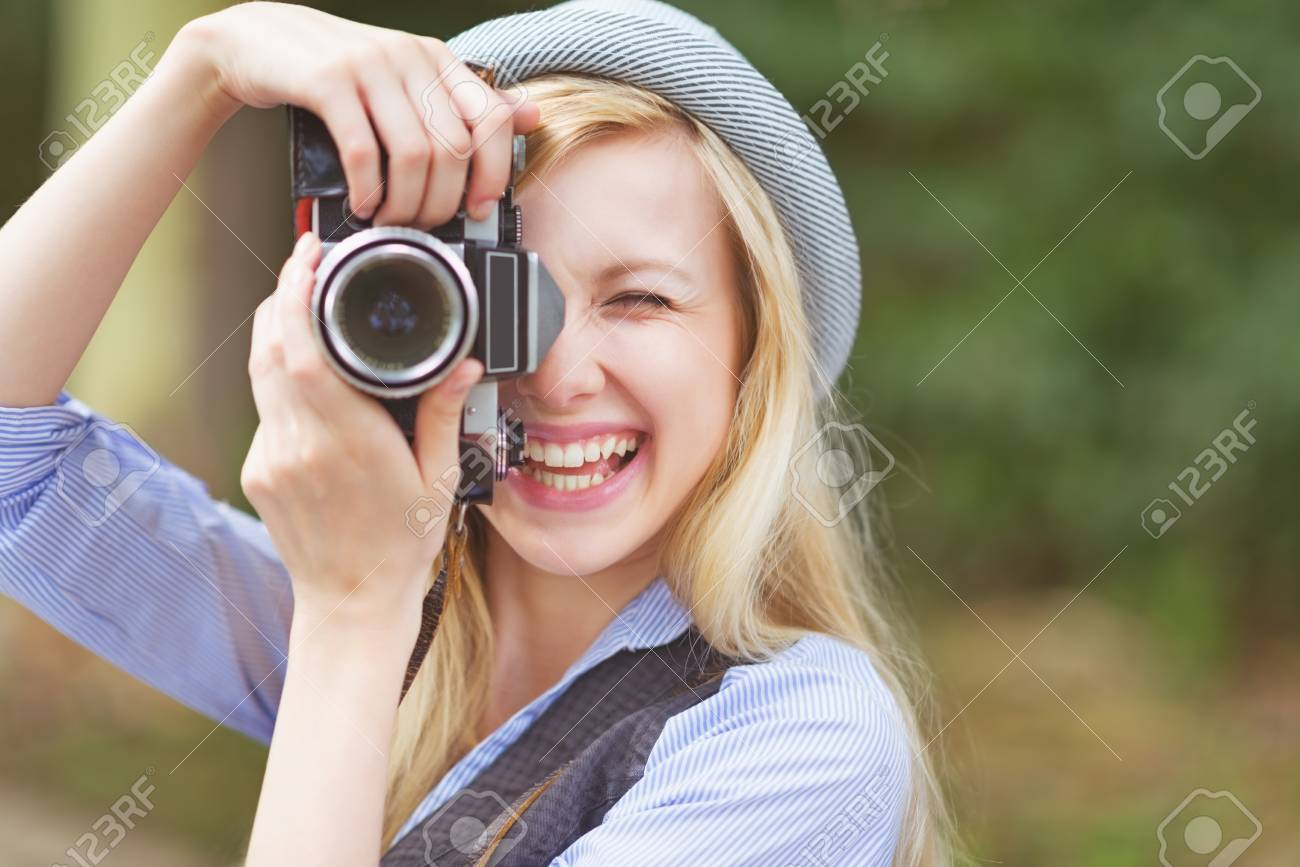 Happy young hipster taking photo with retro photo camera sitting on bench in the park Stock Photo - 26977540