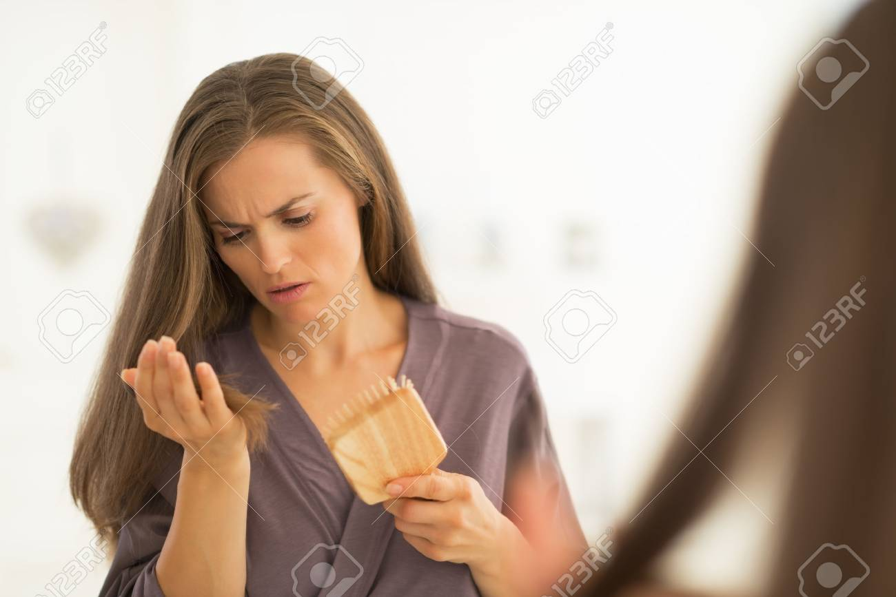 Concerned young woman looking on hair comb after combing Stock Photo - 27700358