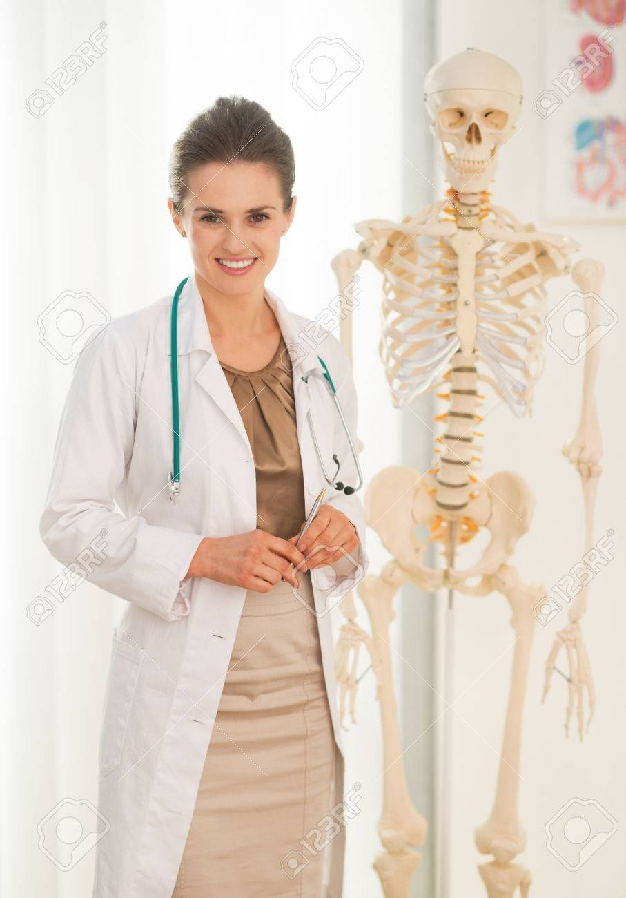 Portrait Of Happy Medical Doctor Woman Near Human Skeleton