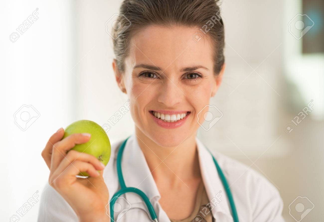 Portrait of smiling medical doctor woman with apple Stock Photo - 28769585