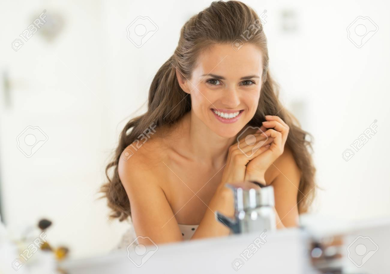 Portrait of smiling young woman in bathroom Stock Photo - 29382394