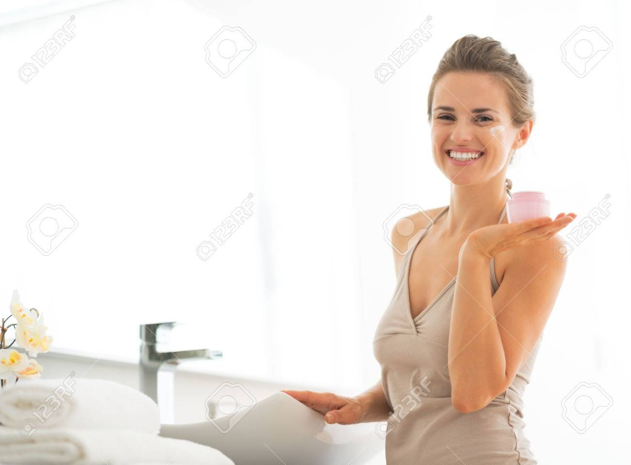 Young woman in bathroom showing cream Stock Photo - 29004537