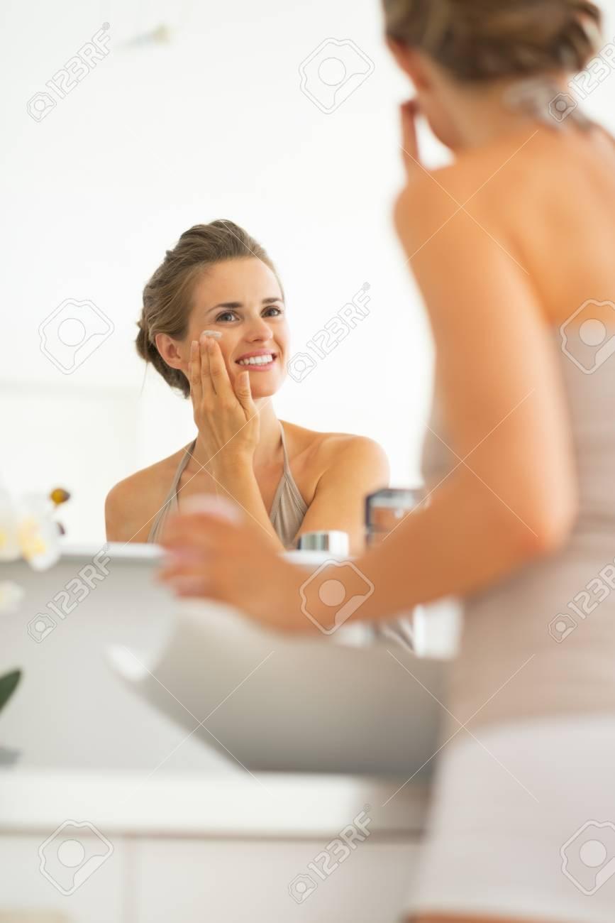 Happy young woman applying cream in bathroom Stock Photo - 29004540