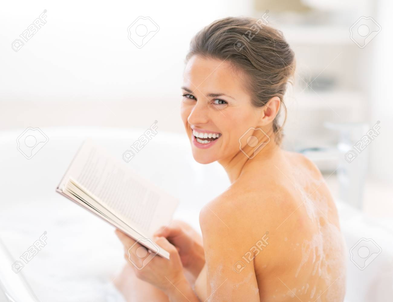 Portrait of happy young woman reading book in bathtub Stock Photo - 29338186