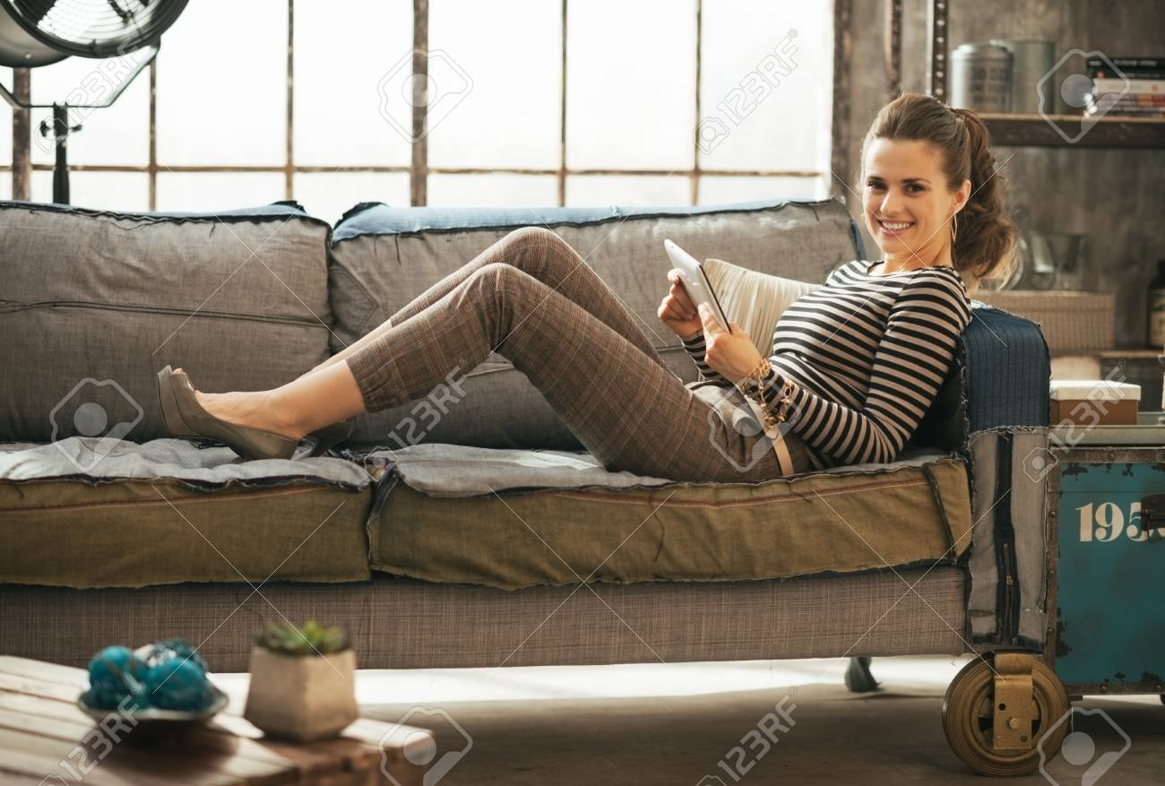 Smiling young woman laying on divan and using tablet pc in loft apartment - 40310543