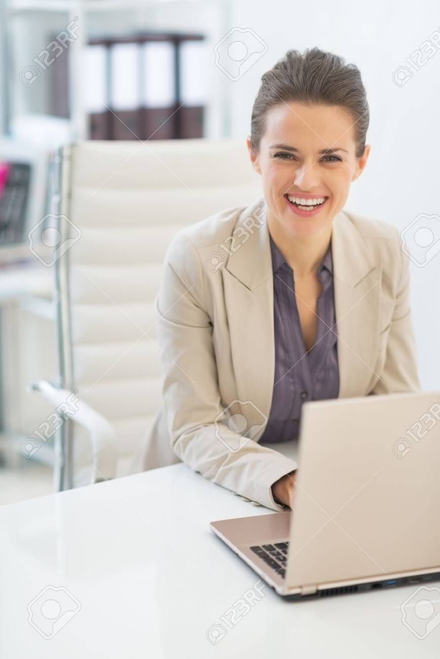 Happy business woman working on laptop in office Stock Photo - 29947684