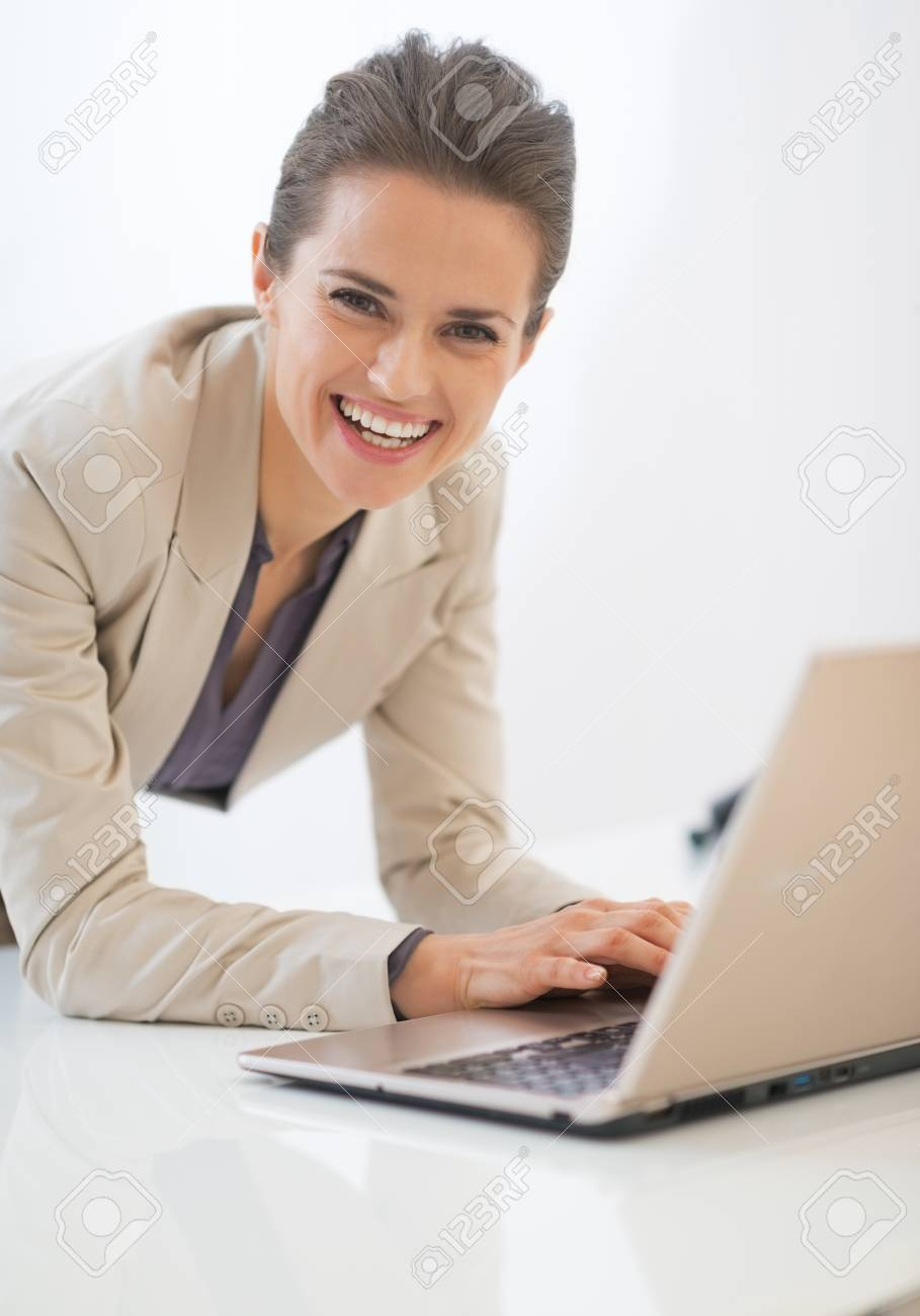 Smiling business woman working on laptop in office Stock Photo - 29996963