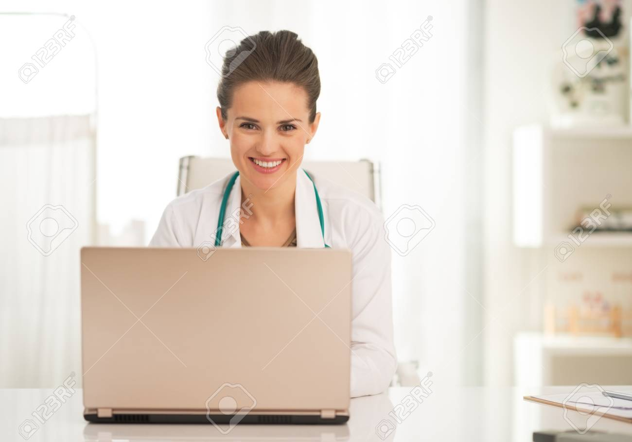 Happy doctor woman working on laptop in office Stock Photo - 30972985