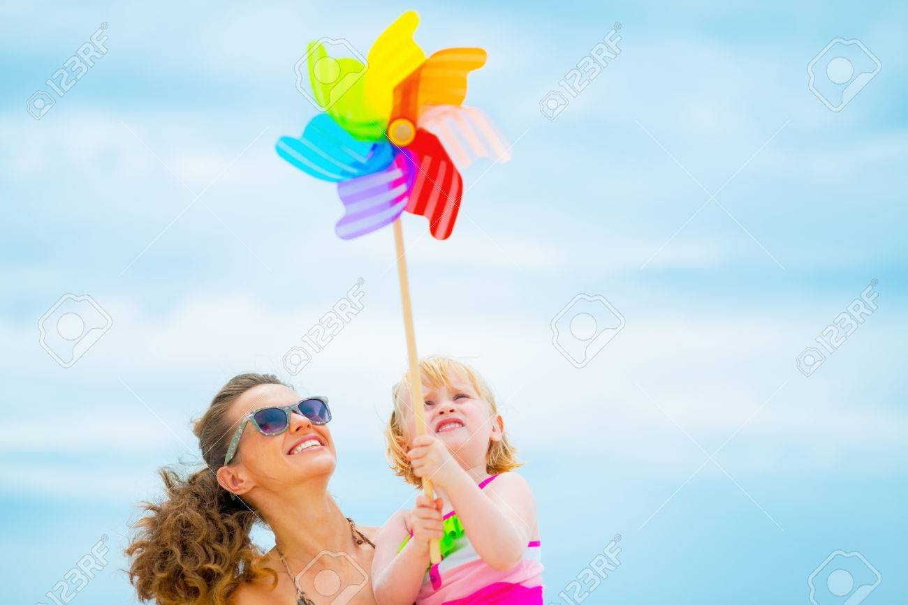 Happy mother and baby girl holding colorful windmill toy - 31329355