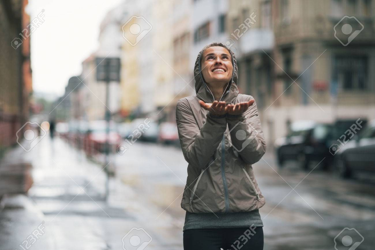 Happy fitness young woman catching rain drops in the city - 31652137