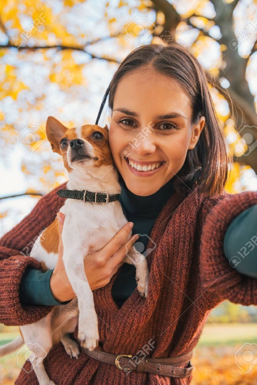 Portrait of smiling young woman with dog outdoors in autumn making selfie - 40310899