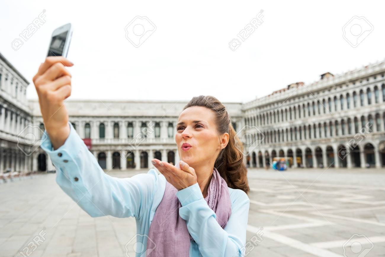 Young Woman Blowing Kiss And Making Selfie On Piazza San Marco ...