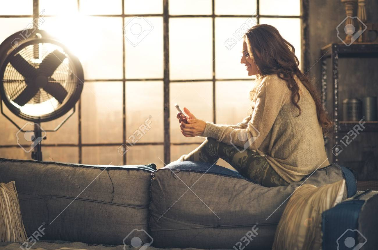 Seen from the side,a brunette woman is smiling, looking down at her phone sitting on the back of a sofa. Industrial chic ambiance and cozy atmosphere, sunlight is streaming through the loft window. - 40213899
