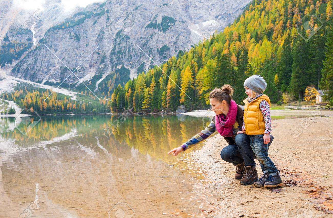 A mother, kneeling next to her daughter on the shores of Lake Bries, is pointing into the water. The colours of their hiking gear reflect the autumn foliage. - 40213986