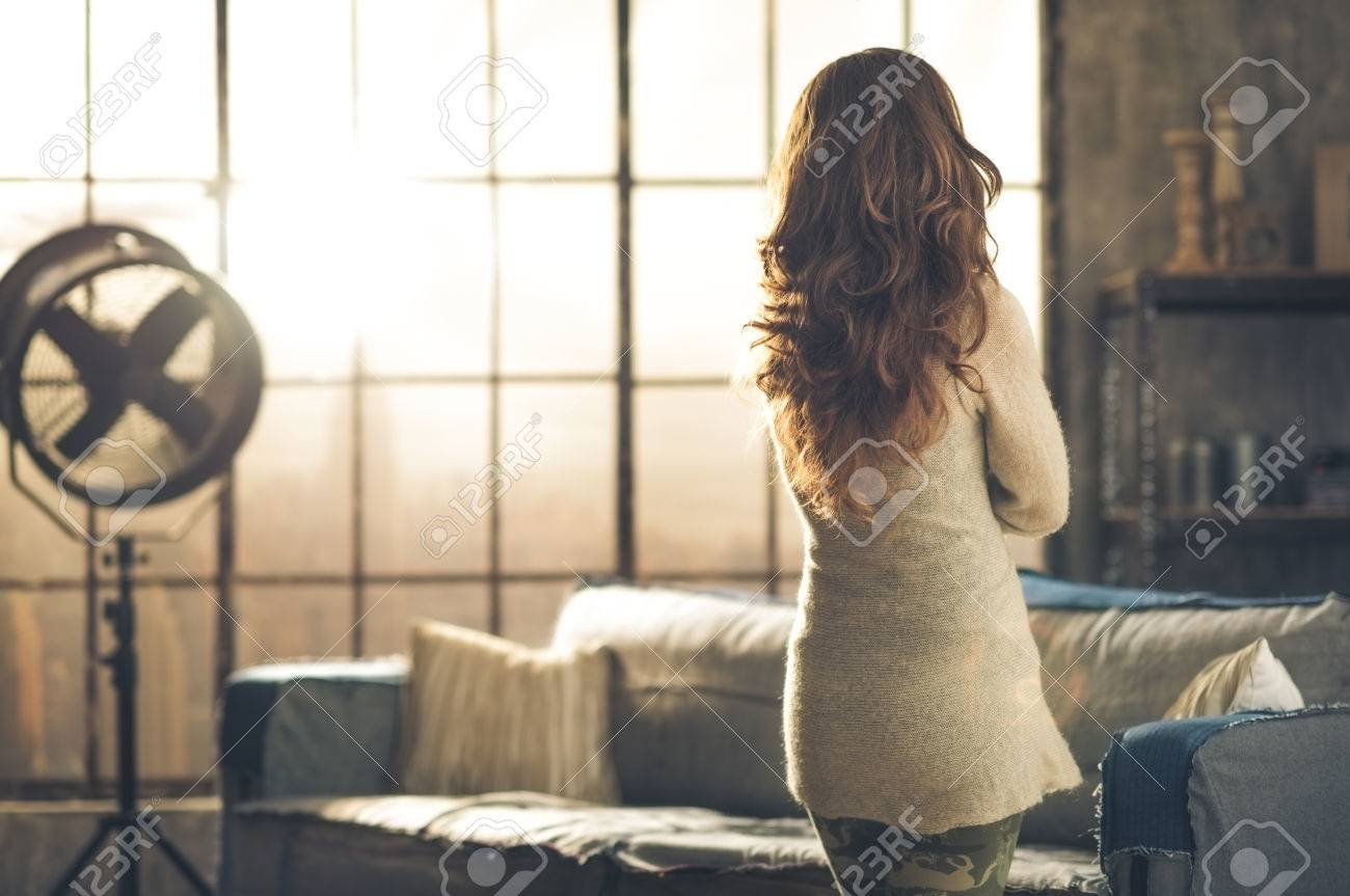 Seen from behind, a brunette woman in comfortable clothing is standing in a loft living room, looking out the loft window. Urban chic loft decoration details. - 40186473