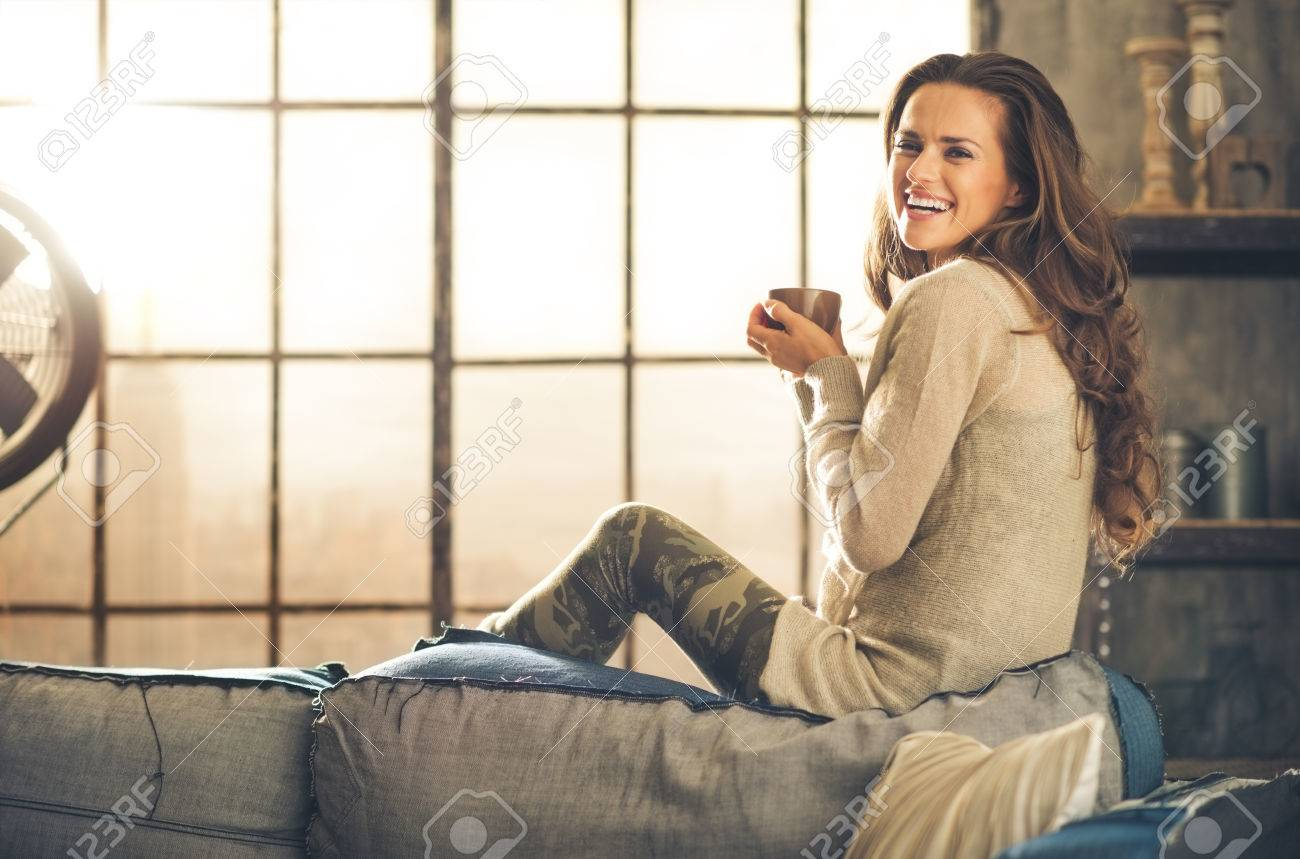 A brunette long-haired woman is seen from the side while sitting on the back of a sofa. She is smiling and holding a hot cup of coffee. Industrial chic background, and cozy atmosphere. - 40217435