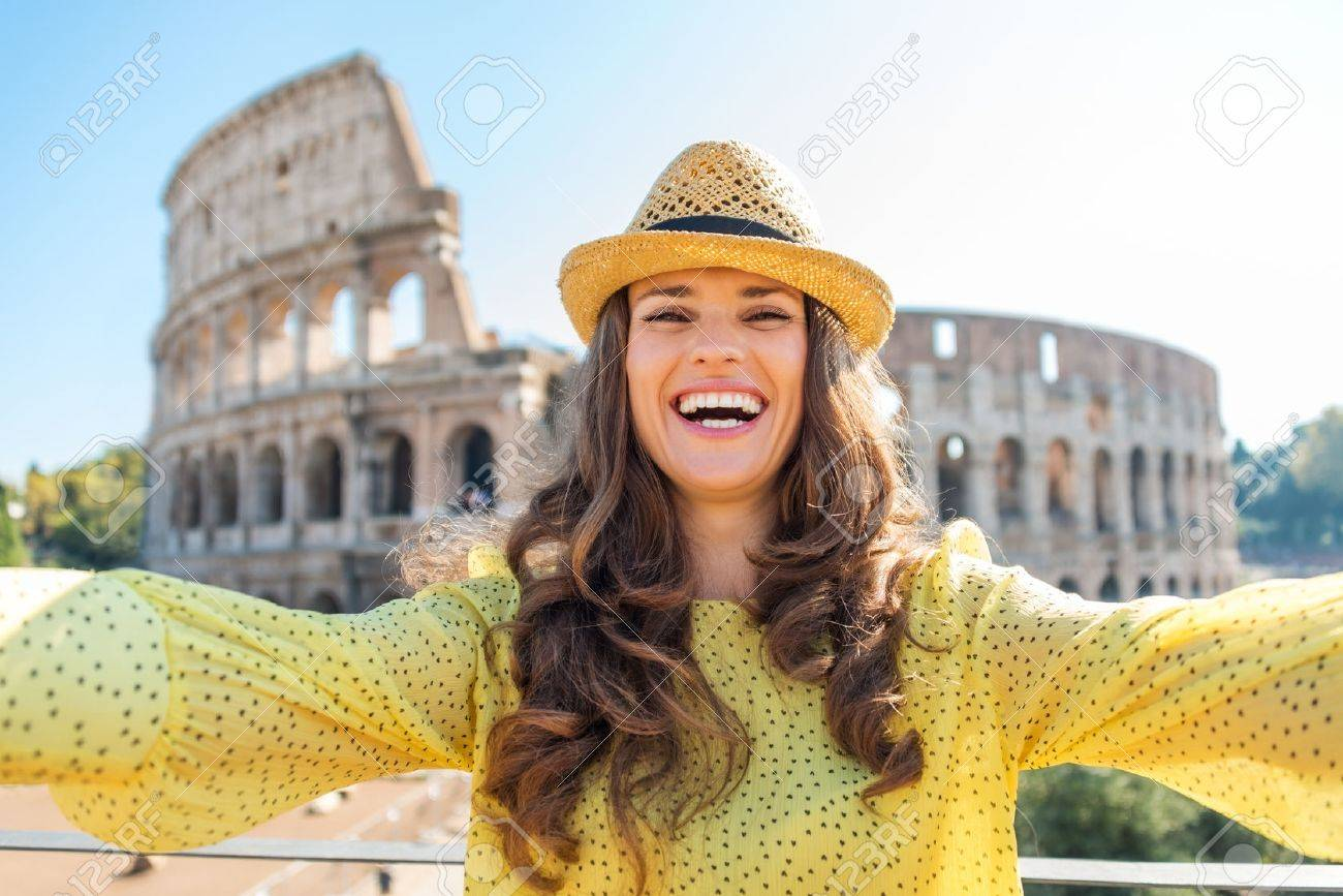A happy, smiling woman tourist in the summer takes a selfie with the Colosseum in the distance. - 40568350