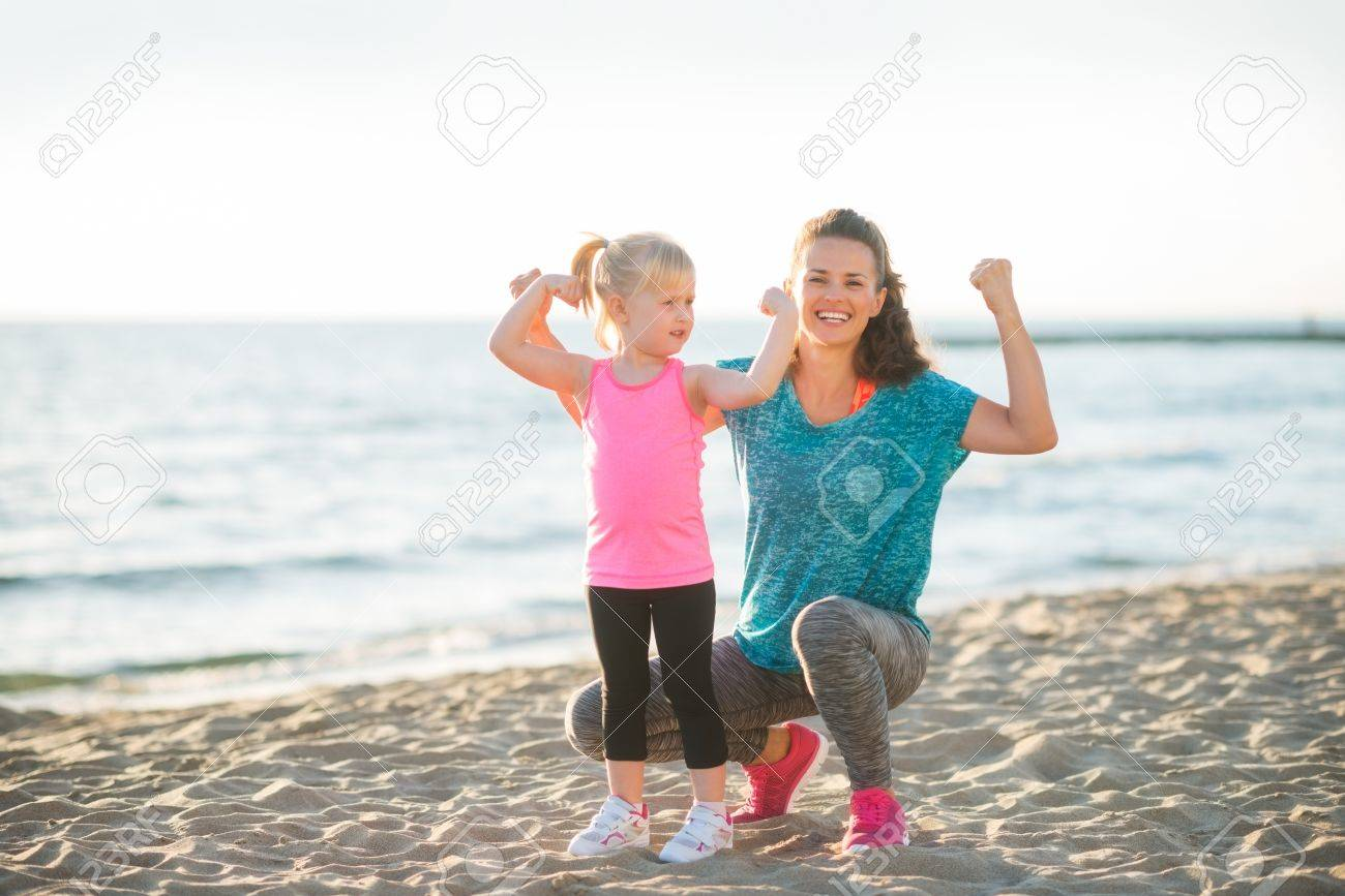 A happy young mother and daughter wearing workout gear are together on the beach at dusk. The mother is kneeling down next to her daughter, and both are flexing their arms to show how strong they are. - 43732966