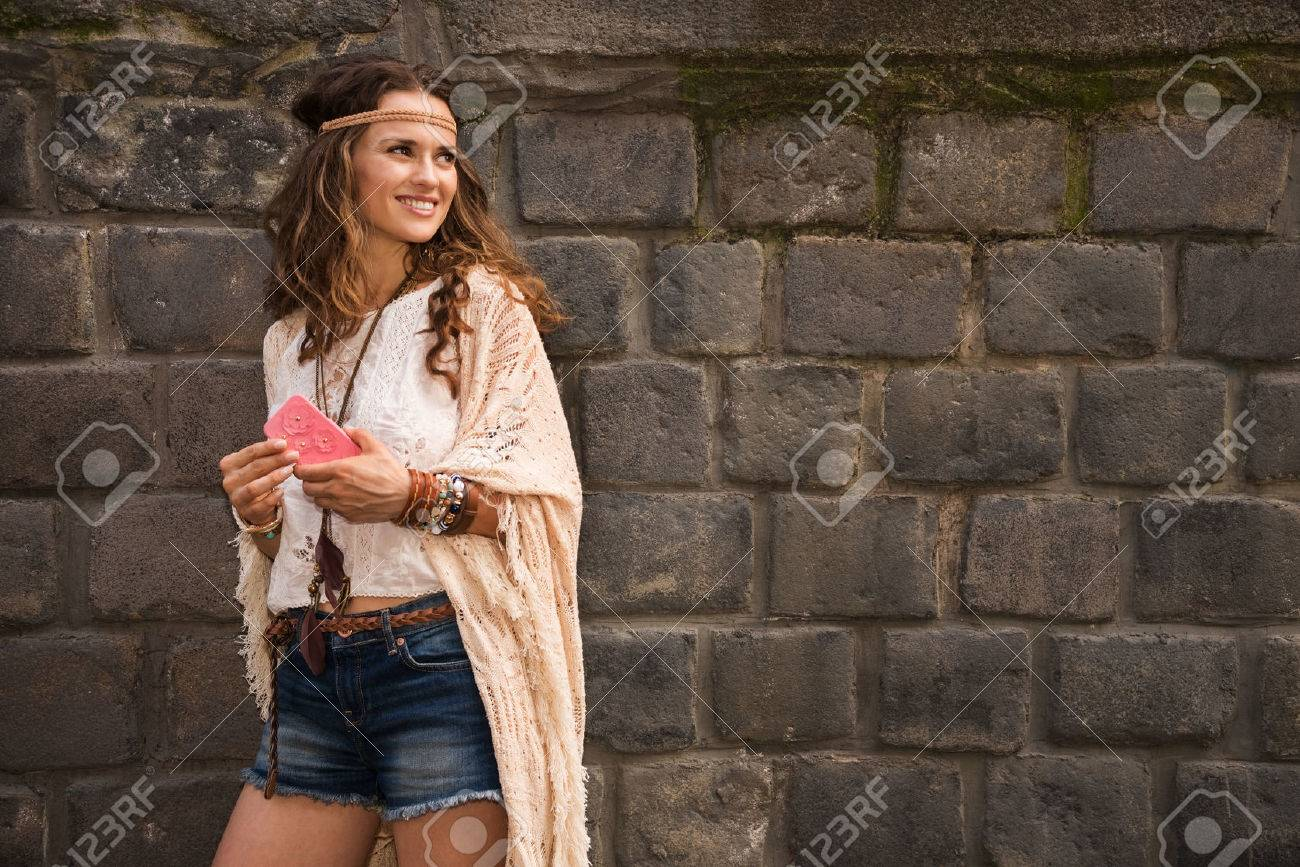 Longhaired hippy-looking young lady in jeans shorts, knitted shawl and white blouse standing near stone wall in old town and holding cell phone - 43887953