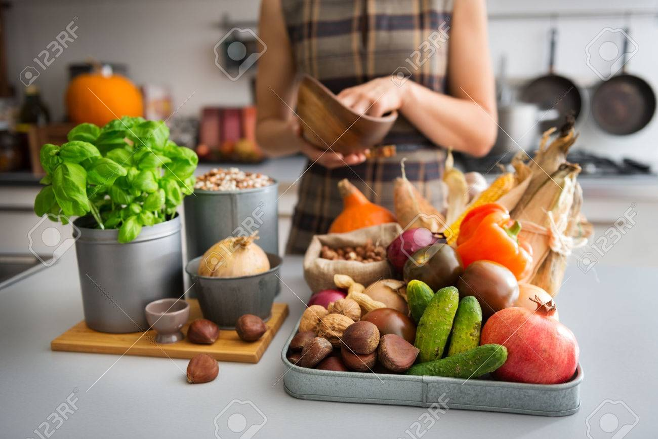 A tray full of Autumn fruits, nuts, and vegetables sits on a kitchen counter. Next to the tray, a wooden cutting board featuring a fresh basil plant and onion promise a delicious meal ahead. - 43733138