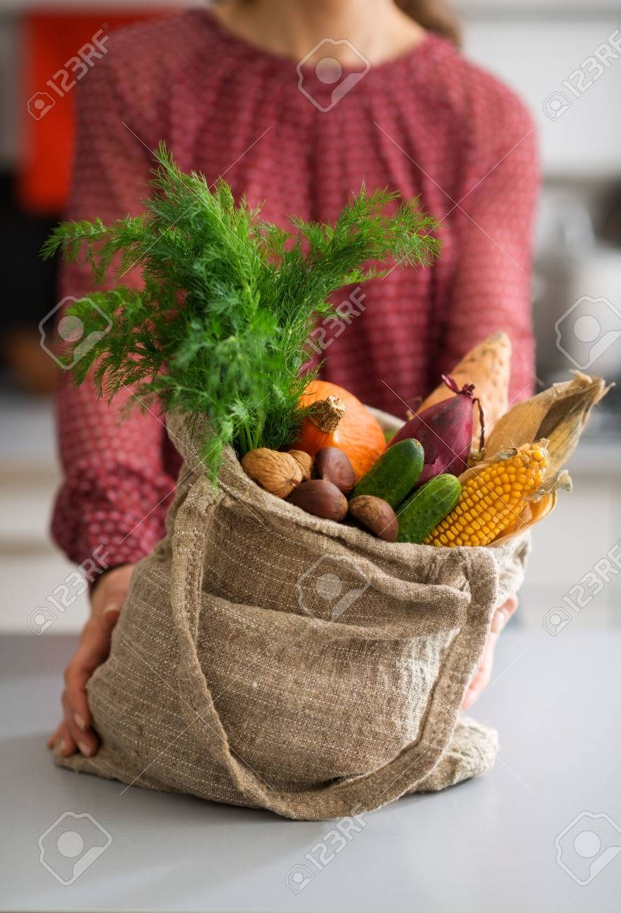An elegant woman in a kitchen is steadying a full burlap sac of fall vegetables. In the sac, we see corn, sweet potato, pumpkin, onion, carrots, and other fall fruits and nuts. - 45021695