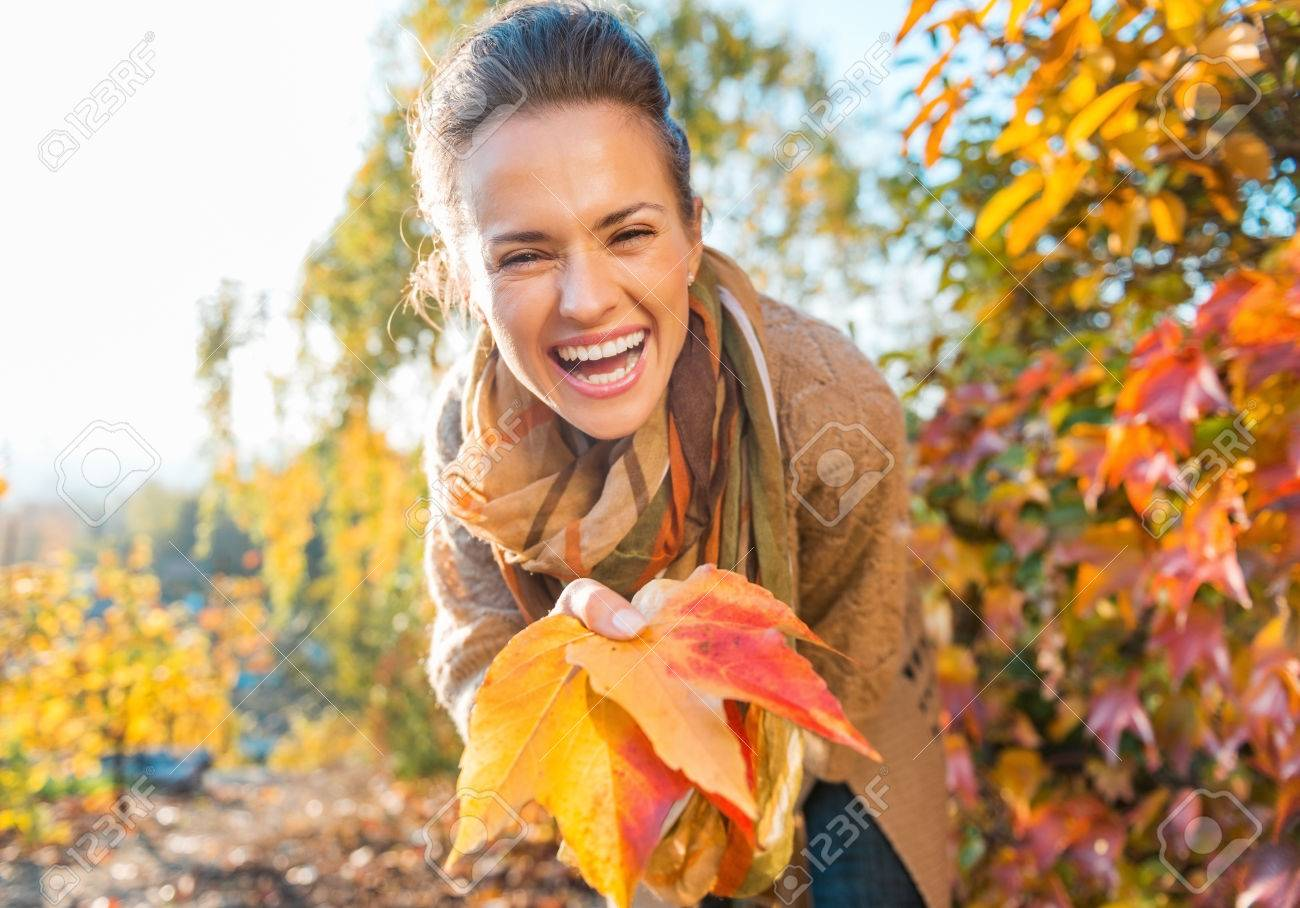Laughing young woman holding colorful autumn leafs in city park - 45387393