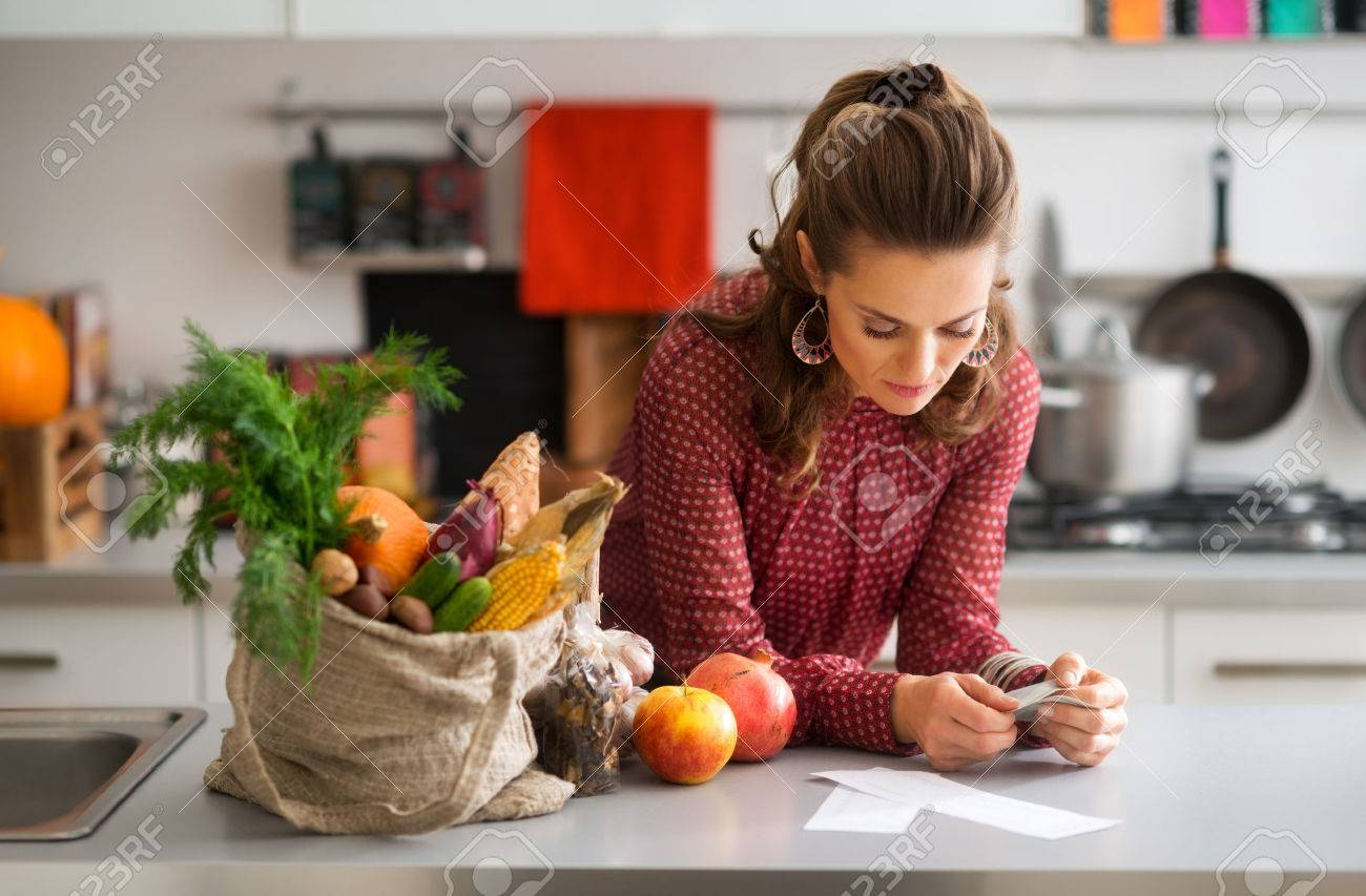 An elegant woman is reading the shopping lists on her kitchen counter. Next to her on the kitchen counter, a burlap sac holds a wide variety of fall fruits and vegetables. - 45379596