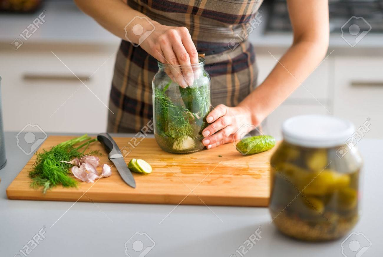 Step by step, the flavors come together. Here, a woman's hands are hard at work, stuffing cucumbers and dill into a pickling jar as she prepares home-made dill pickles. - 45218511