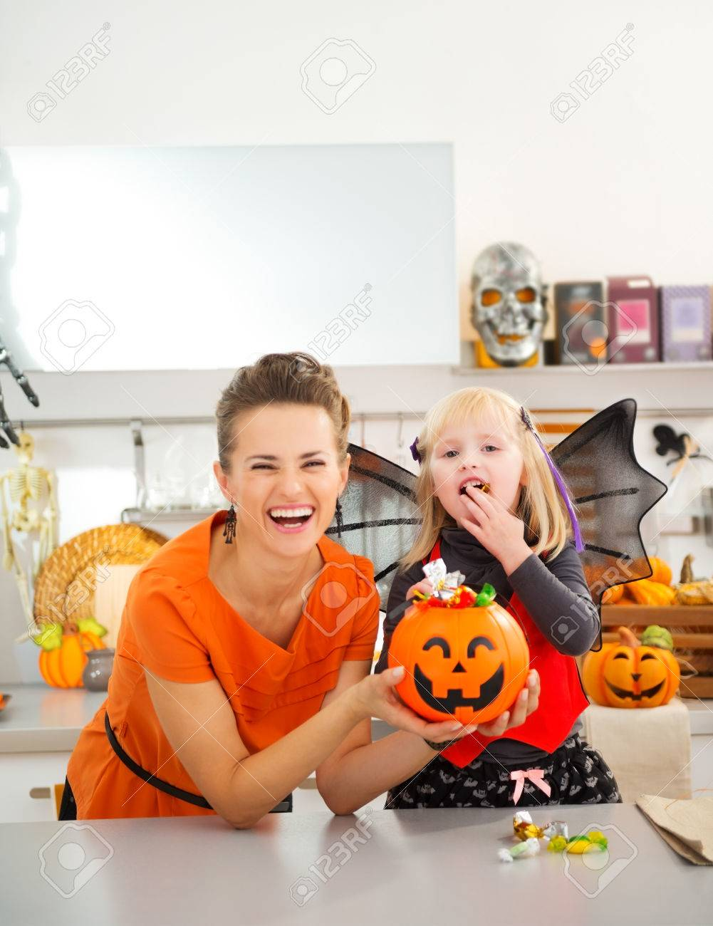Happy young mother with daughter in bat costume eating colorfull halloween candy in decorated kitchen. Halloween Candy is so good. Traditional autumn holiday - 45391819