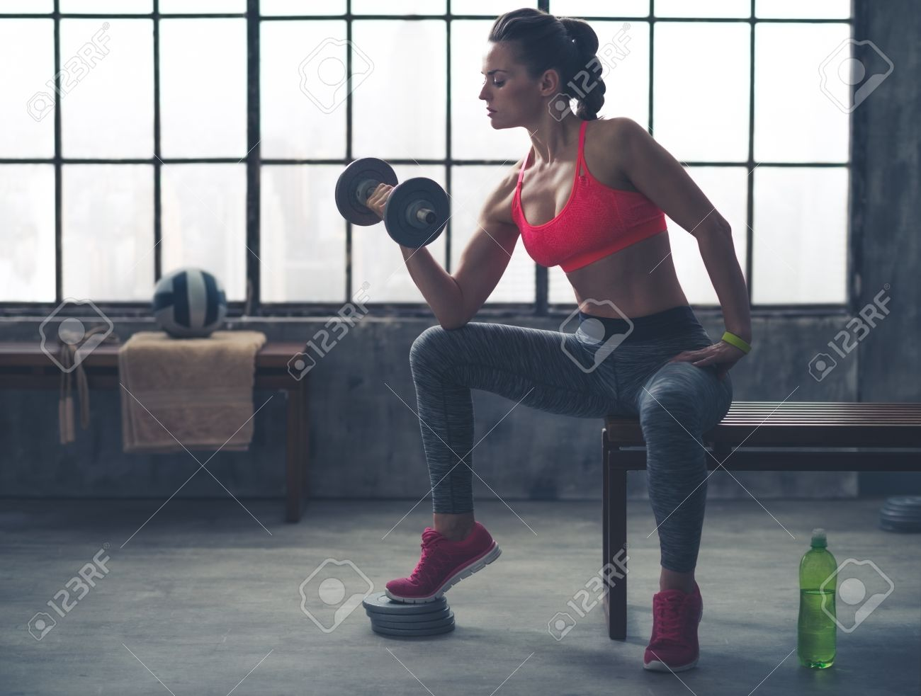 Feel that burn! A fit, sporty young woman is sitting in profile on a bench in profile, lifting weights with one hand, while resting her elbow on her knee. - 46425694