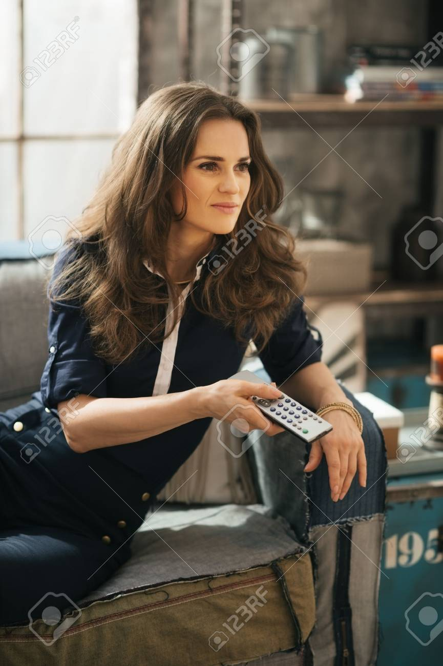 Stylish elegant woman relaxing on sofa and watching tv in loft apartment. Urban chic loft decoration details and window. Modern lifestyle concept. - 46668573