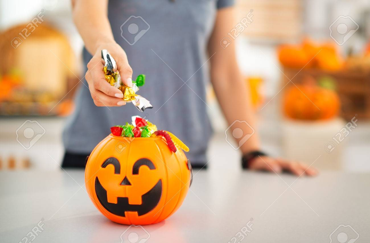 Halloween candy is never too much! Closeup on woman putting trick or treat candy in halloween Jack-o-Lantern bucket. Traditional autumn holiday - 47464038