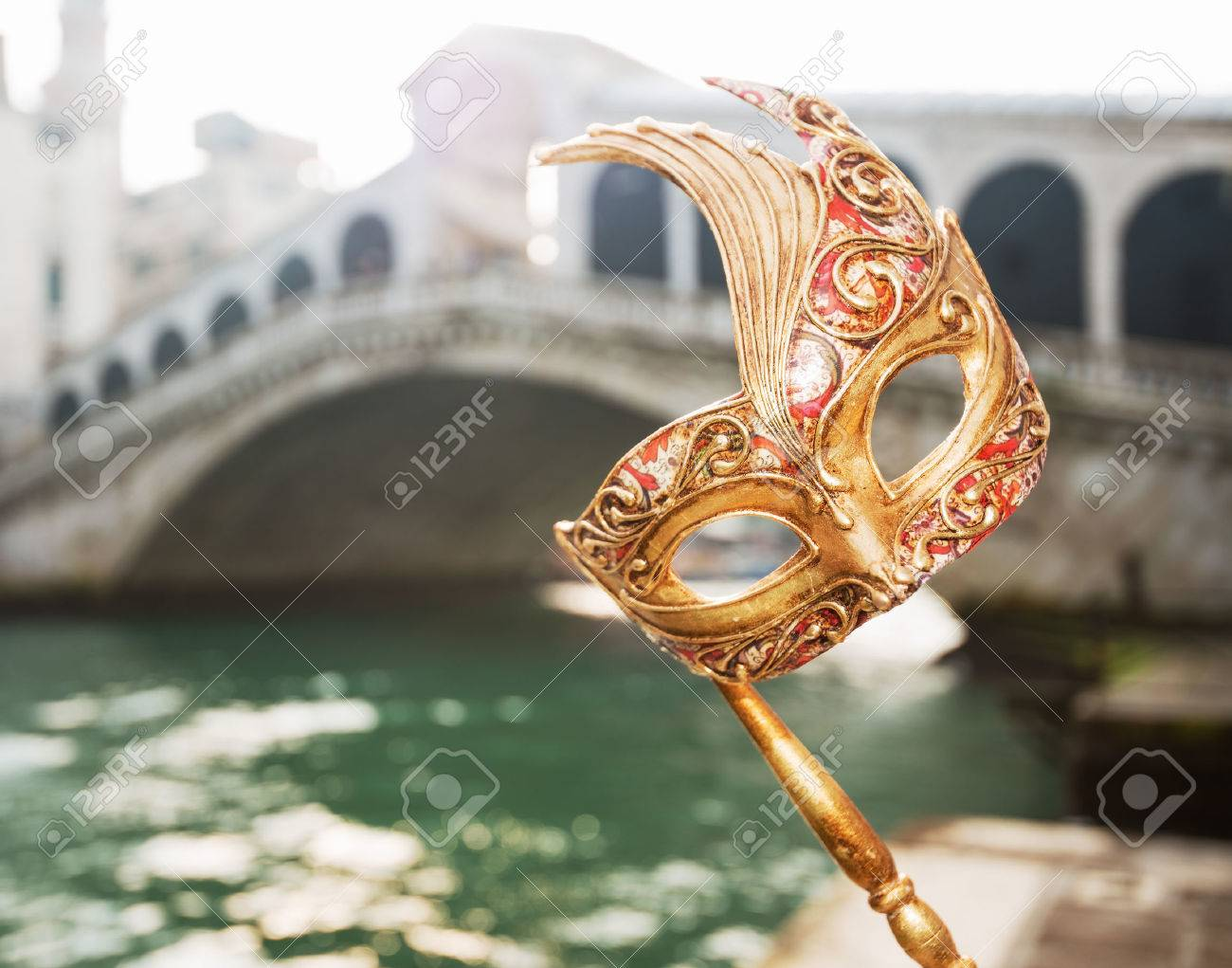Ultimate getaway shortcut - start New Year going on Carnival in Venice, Italy. Closeup on woman hand holding Venice Mask in the front of Rialto Bridge - 53610757